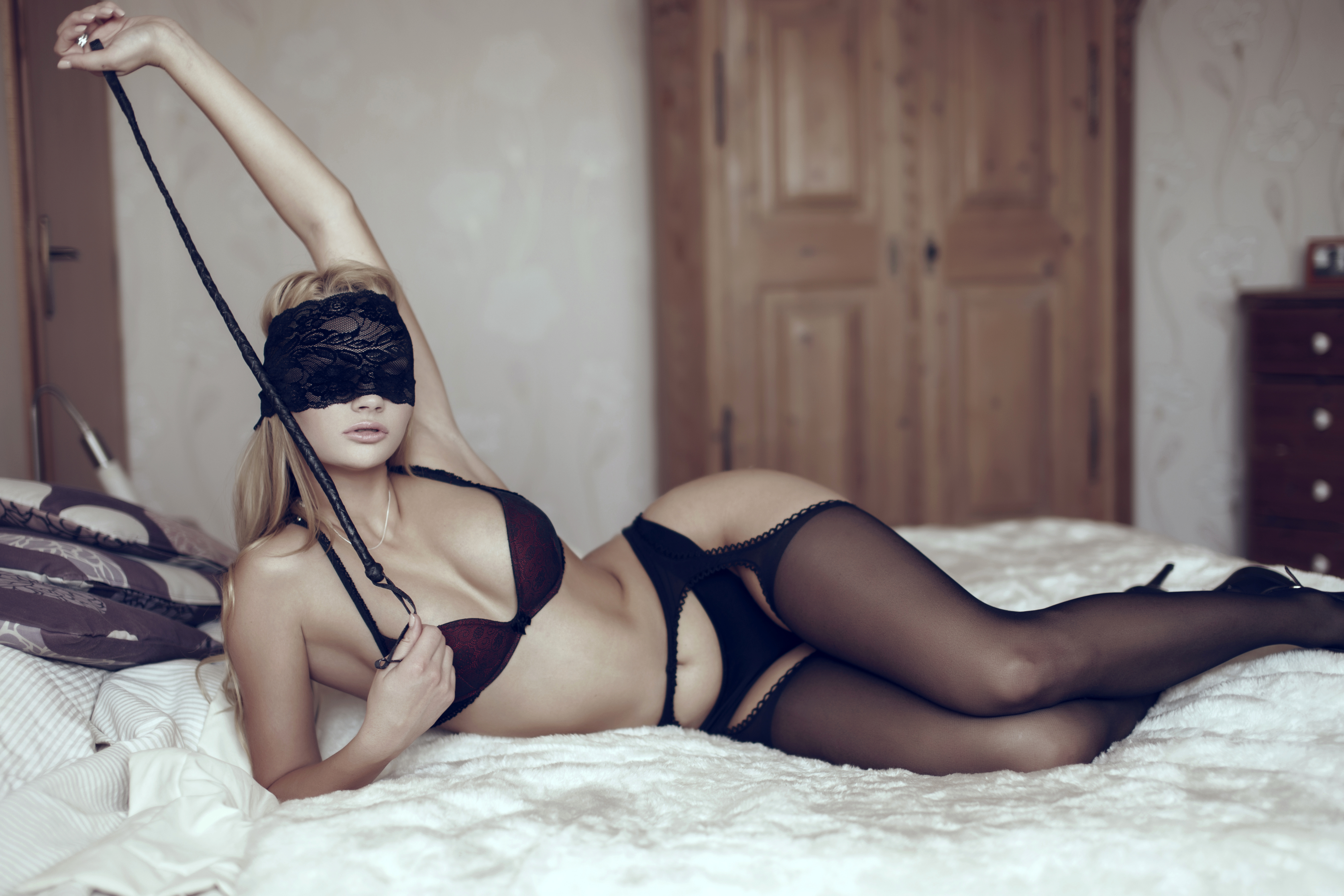 Sexy woman in lace eye cover with whip